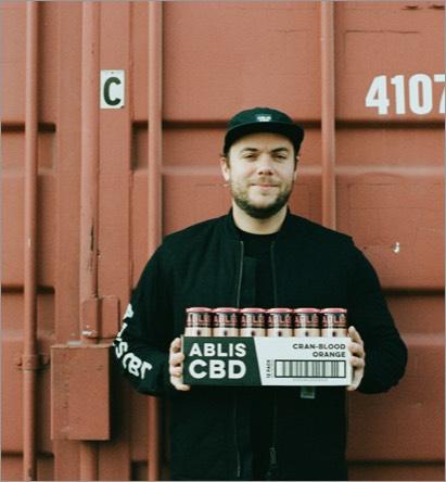 Man holding a case of Ablis cran-blood oragne